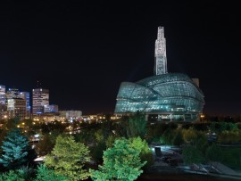 The glass tower and facade of the Canadian Museum for Human Rights give the building a glowing presence in the Winnipeg cityscape.