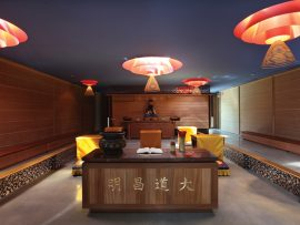 Custom luminaires lend a red glow to the skylit interior, and are designed for suspending incense coils.