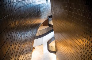 Glazed terracotta tiles clad the interior volumes, conceived as towers containing the exhibition spaces.