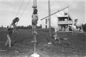 Children play in front of the wood-clad house in 1974. Photo: Nancy Willis
