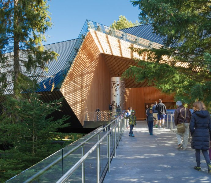 The bridge leading to the main entrance is capped by a contemporary interpretation of a totem pole. Photo: James Dow / Patkau Architects.