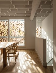 A lattice-like wood screen provides a porous enclosure for the upper unit's front balcony.
