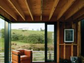 Wood framing is left exposed throughout much of the house, which is a model for a minimal dwelling.