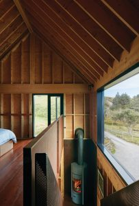 The upper level of the house is a loft-like sleeping area, warmed by the ground-floor wood stove.