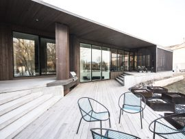 Floor-to-ceiling windows and a cascade of terraces open towards the backyard.