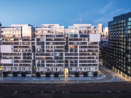 A playful façade composition gives individual identity to the condomiumum units in the white Phase 2 building