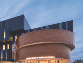 Lazaridis Hall's bold massing is bookended by wood-clad cylindrical volumes that house auditoriums.