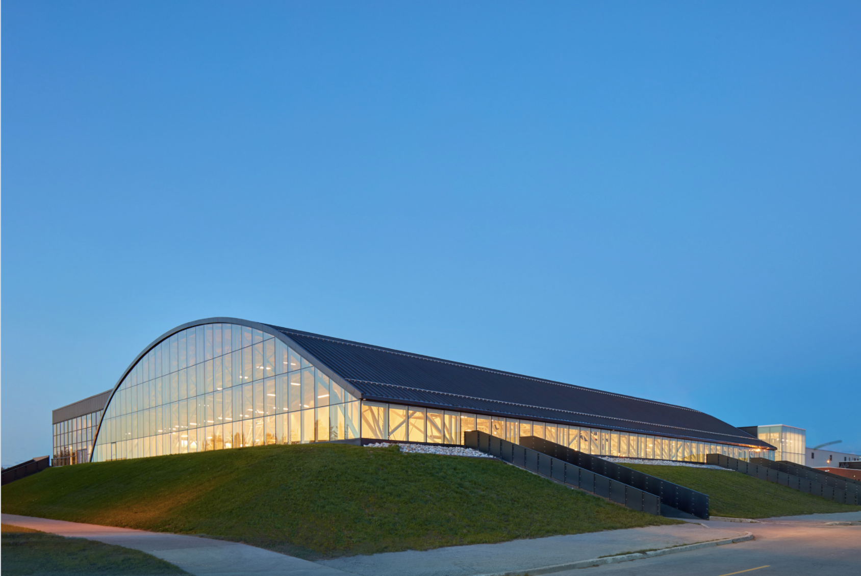Instead of demolishing and replacing a 1970s arena as originally mandated, MJMA advocated for adaptively reusing it. Glazing was added to the sides and end of the barrel-vaulted volume, maintaining its structural integrity while bringing daylight to the interior. Photo by Shai Gil