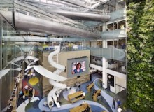 Atrium of Quadrangle Architects' Corus Quay project, shot from the third-floor bridge. The five-storey space brings light into the central areas of the large 70,000-square-foot floor plates. There are bridges on the third, fourth and fifth floors, allowing ease of access across the atrium. The three-storey double TV studio in the centre of the space acts as a platform for the top of the studio lounge, a large TV wall to the south, an acoustic object in the large, hard-surfaced space and a launch point for the slide.