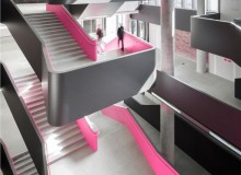 The striking multi-level Atrium at Rotman School features a serpentine staircase accented with hot pink that brightens the monochrome interior. Credit: Tom Arbun Photography Inc.
