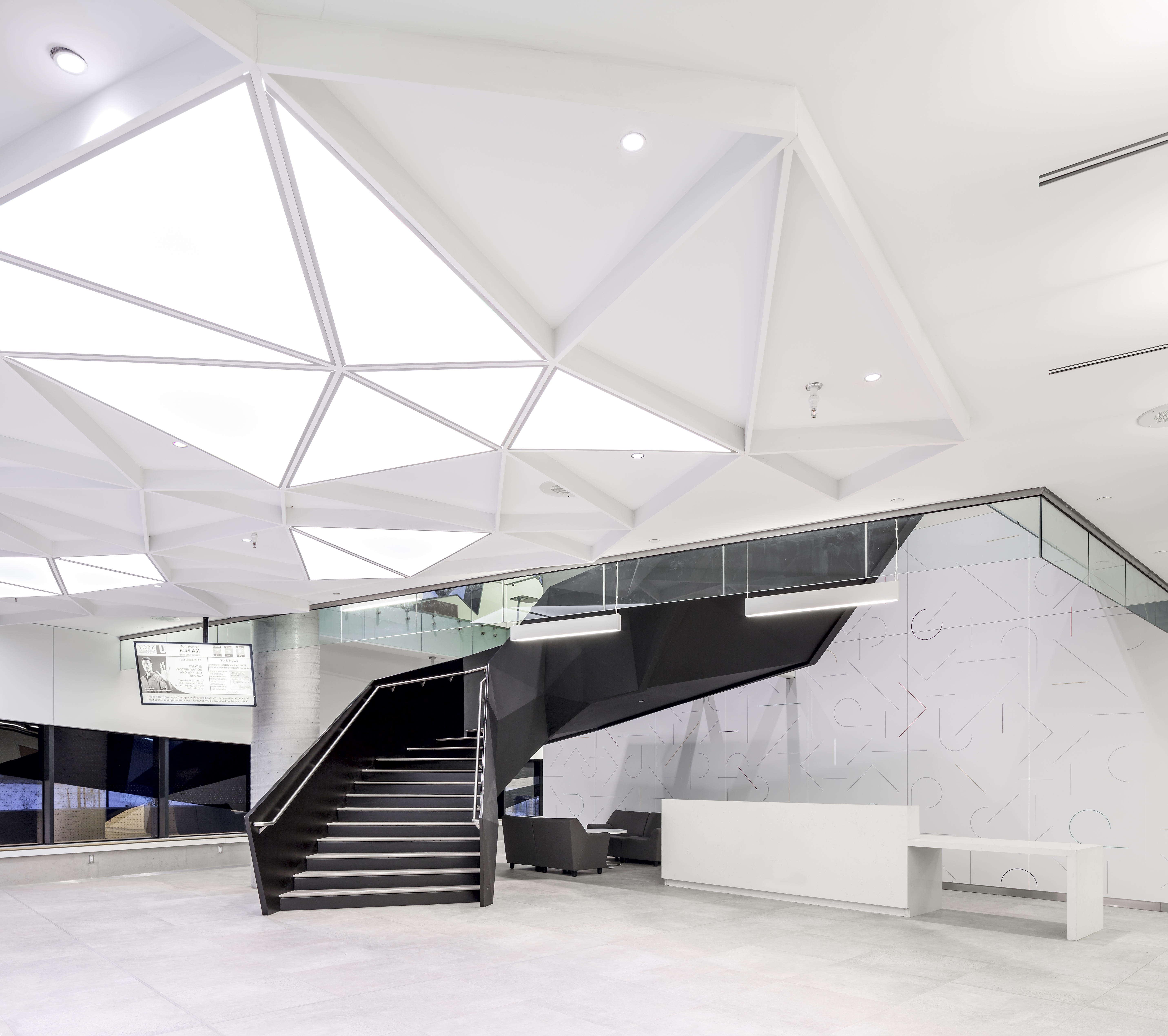 """The dynamic triangle motif carries through the building like a brand icon, visible here in the main lobby's fluorescent """"skylights"""" and U-shaped staircase constructed from welded triangular slabs of steel. Photography by Doublespace Photography"""