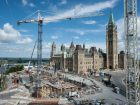 Construction of Phase 1 of the Visitor's Welcome Centre, with the Ottawa River, the Centre Block and the Peace Tower in the background.