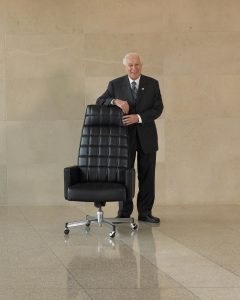 Saul Feldberg, founder and chairman of The Global Group, stands beside the Executive 105, which in effect pioneered the mid-market segment of the office furniture industry in North America.