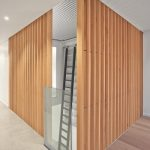Vertical-grain Douglas fir slats replace guard rails on stairs and mezzanine. Photography by RobitailleCurtis