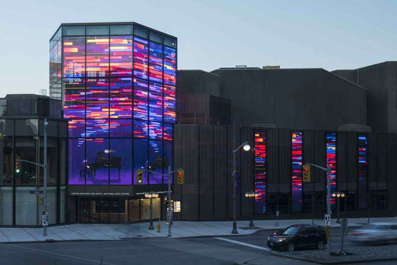 "The next stage of renewal at the National Arts Centre in Ottawa will be unveiled on New Year's Eve. The Kipnes Lantern is a three-storey, multi-sided signature element of the NAC's architectural rejuvenation, a $225-million project by Diamond Schmitt Architects. Positioned above the new Elgin St. entrance, the Lantern features the largest transparent LED screen in North America. The Lantern will showcase productions presented not only on NAC stages but also on the stages of performing arts organizations across Canada. The idea to create a ""fifth stage"" at the four-stage arts complex came from NAC CEO Peter Herrndorf and architect Donald Schmitt during the planning process to transform the mid-century Brutalist structure into an inviting and transparent facility that engages with the city. ""The unique see-through technology of the screen complements the transparency established in the new public wings that enwrap the NAC and provide connection with downtown Ottawa and outstanding views of nearby landmarks,"" said Donald Schmitt, Principal, Diamond Schmitt Architects. ""The Kipnes Lantern is a beacon for the performing arts, showcasing the breadth and excellence of the music, theatre and dance being produced across Canada,"" said Peter Herrndorf. In addition, digital 'shorts' created by Montreal's Moment Factory, will convey moments of wonder and whimsy throughout the year. The Lantern will also recognize events of national importance such as Canada Day, Remembrance Day, and National Indigenous Peoples Day. Vancouver-based company ClearLED provided the transparent digital screens on four sides of the Lantern in addition to smaller fin screens along the Elgin Street façade. The National Arts Centre rejuvenation was inaugurated on July 1st with the opening of improved spaces for performance, new wings for audience and presentation events and reorienting the building to open onto the city after having its concrete back turned on Ottawa for 50 years. New events space along the Rideau Canal and further enhancements to the NAC's theatres will open in 2018."