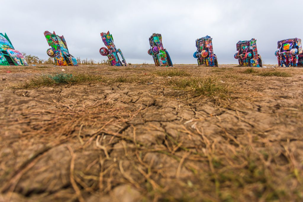 Cadillac Ranch, painted and colourful cars in the ground.