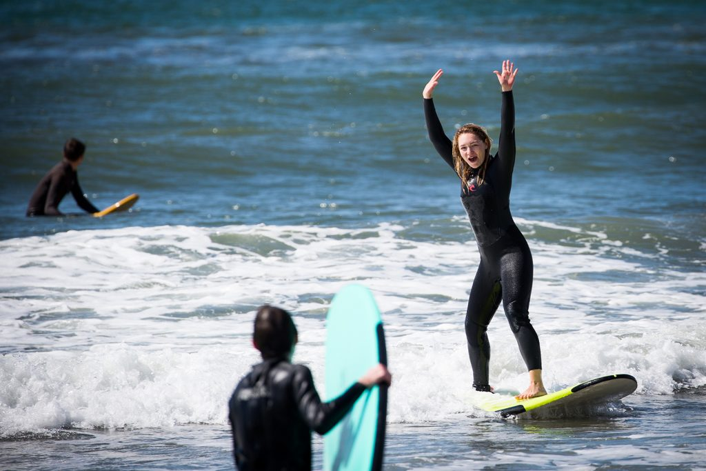 A woman riding into shore on her surf board cheering over her success.