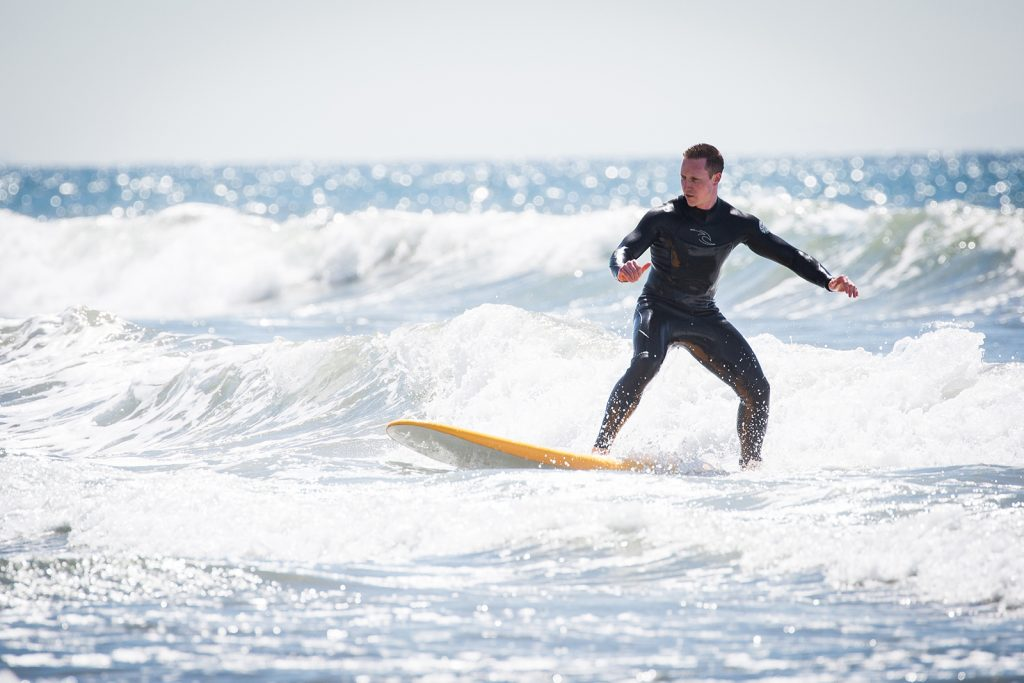 Man catches a wave at surf lessons in Santa Monica