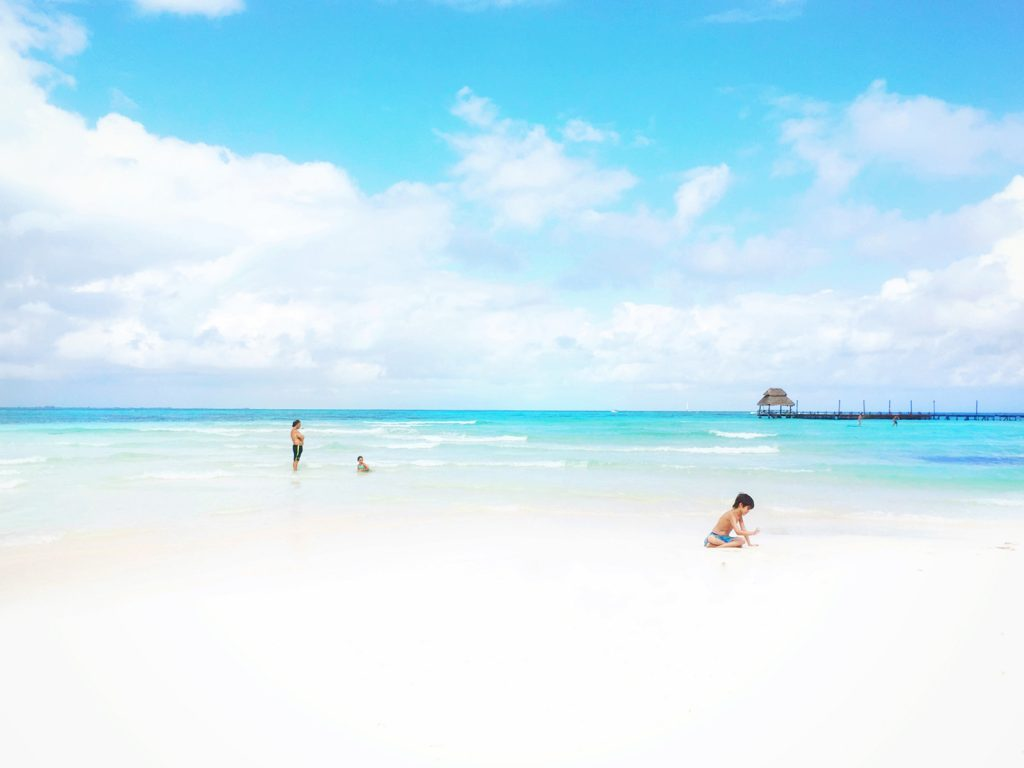 Children play in the white sand at Playa Norte on Mexico's Isla Mujeres.