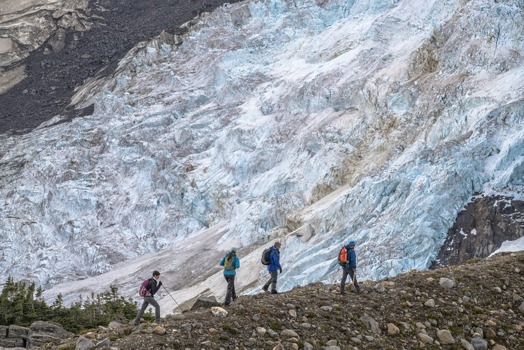 Hikers in the shadow of a glacier.