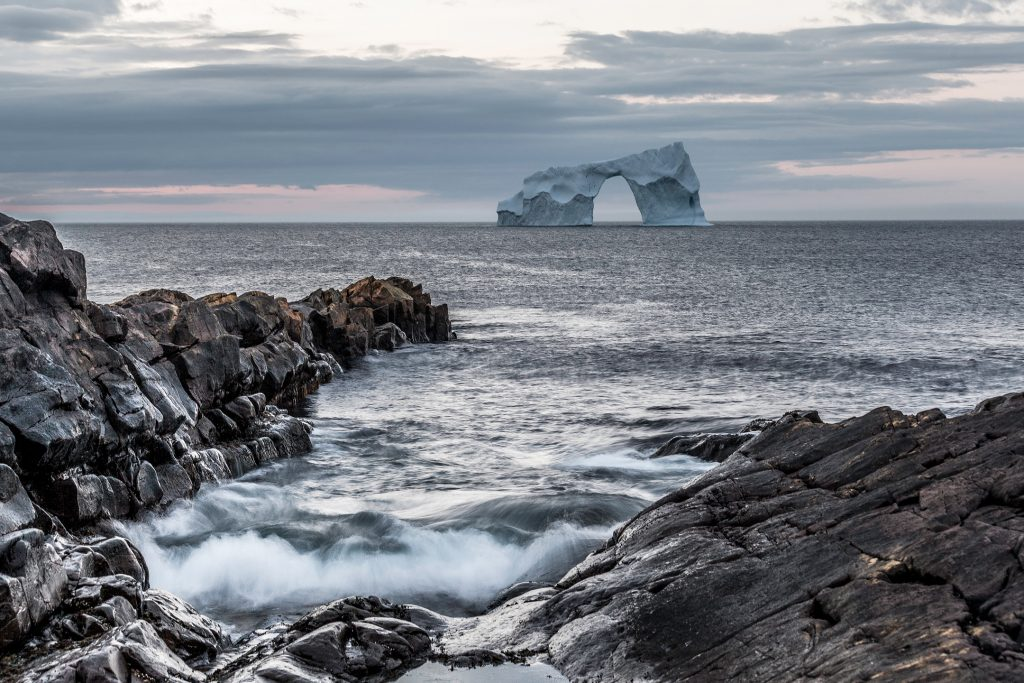 An arched iceberg is seen a short distance from a rocky shore with waves