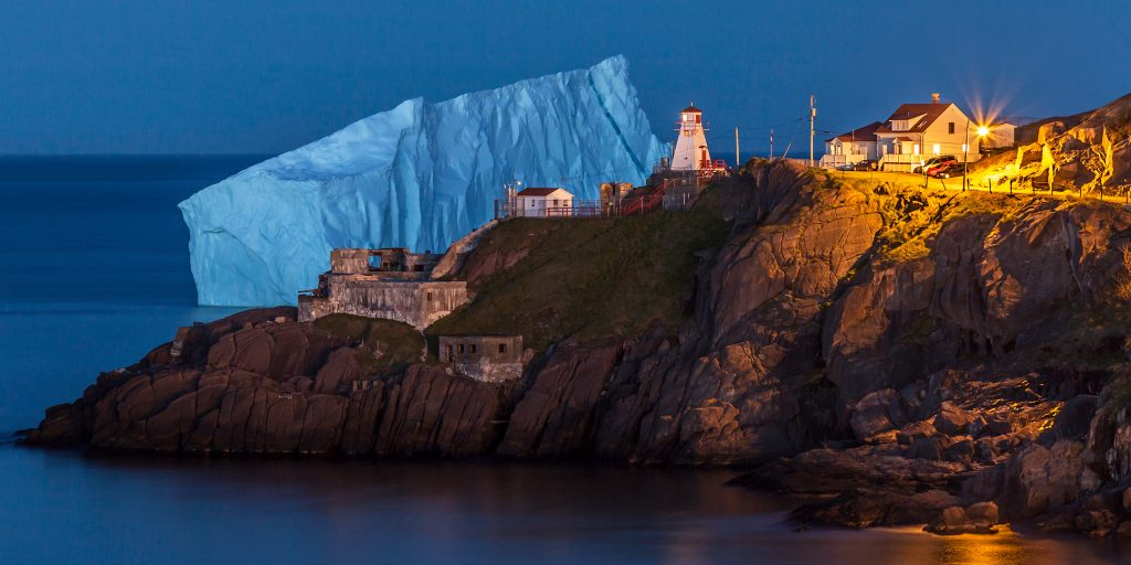 A massive iceberg at blue hour behind a peninsula with a lighthouse