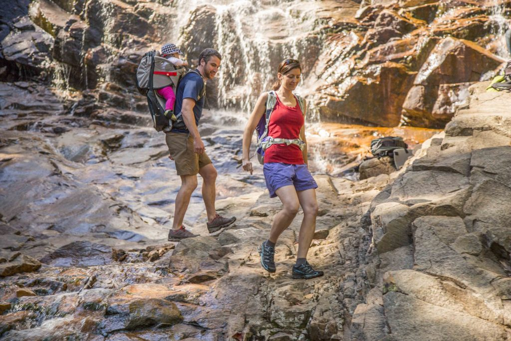 A couple with a baby hiking past a waterfall in Crawford Notch State Park, New Hampshire.