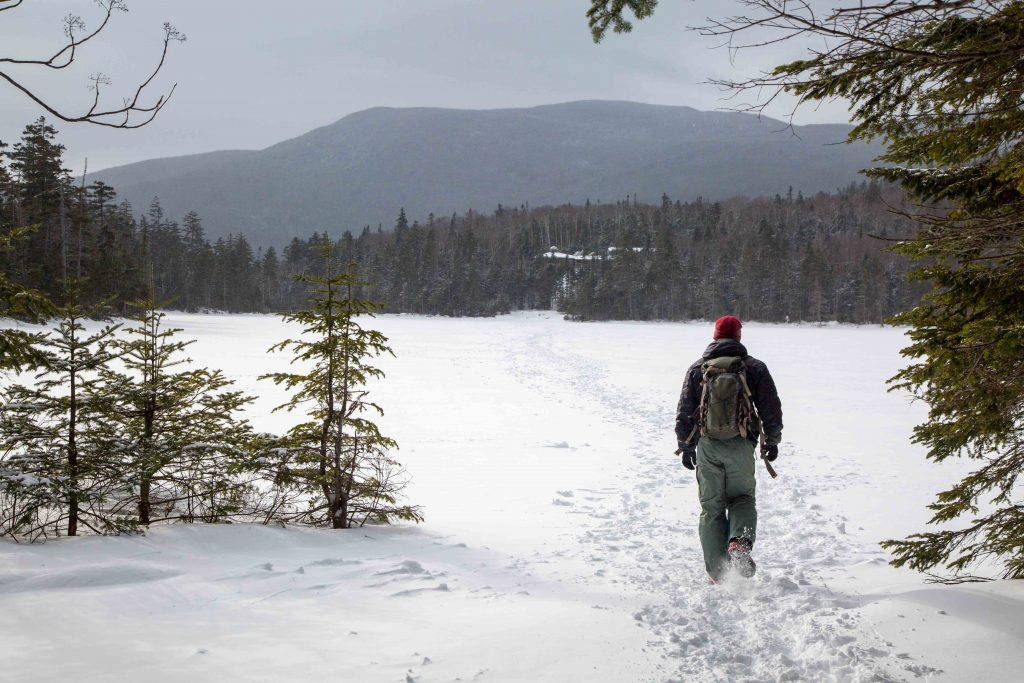 A single person hiking across a snow-covered lake with a view of mountains in New Hampshire