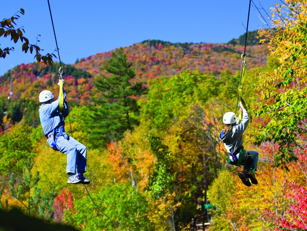 Two people ziplining over mountains with fall colours in New Hampshire