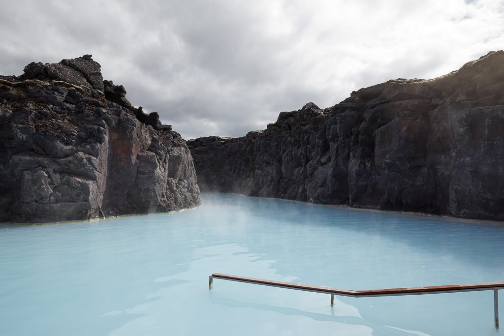 A blue thermal pool in Iceland surrounded by volcanic rock