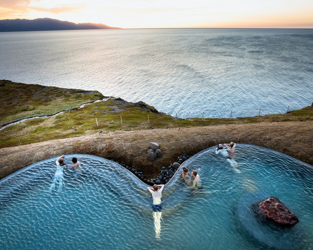 People swimming in a hot pool overlooking the ocean in Iceland