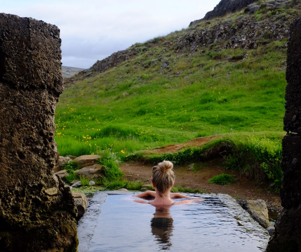 A blonde woman relaxes in a stone-walled hot spring in Iceland
