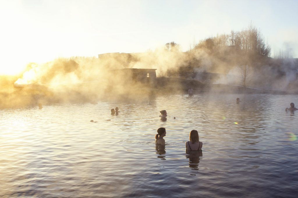 Multiple people bathe in a hot spring at sunset