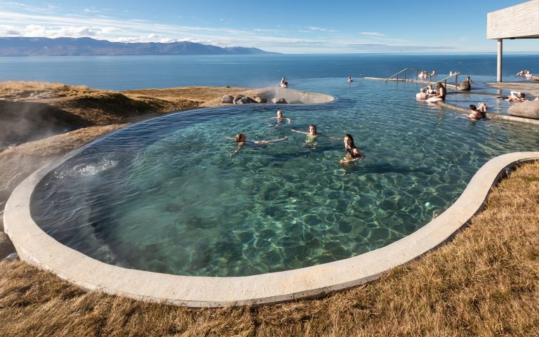 People bathe in a clifftop infinity pool overlooking the ocean on a clear day