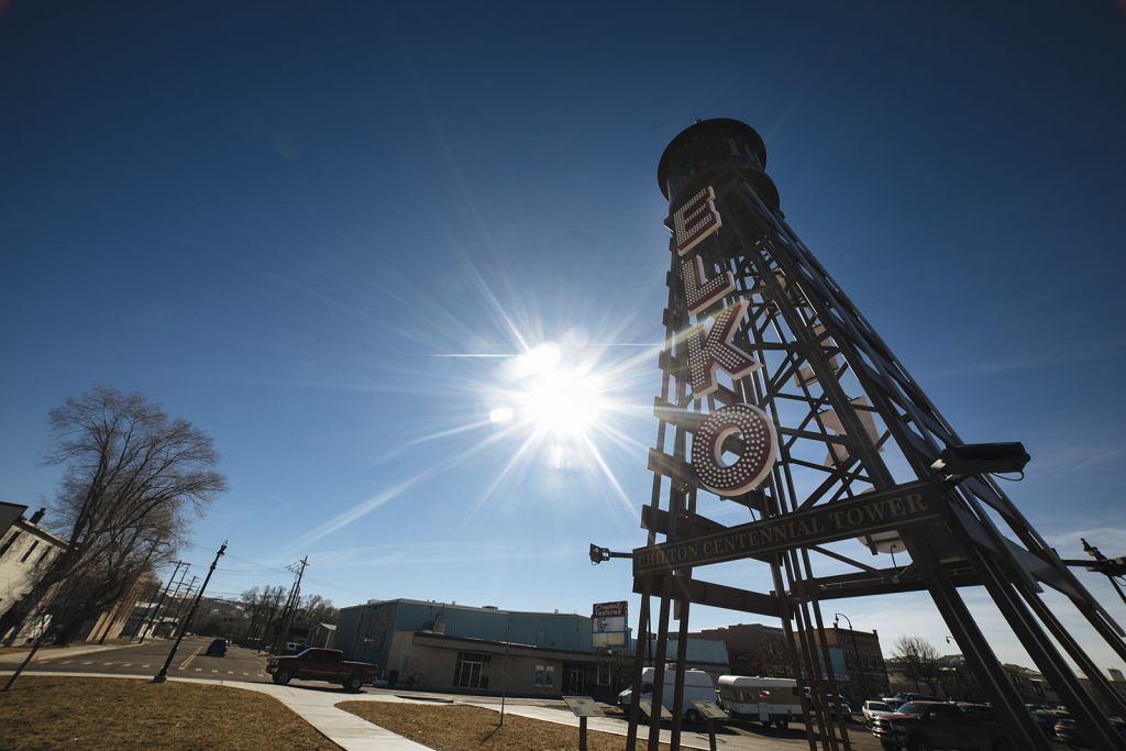 The sun shines behind the Elko Water Tower
