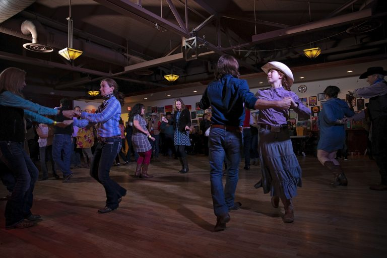 Couples in traditional western dress dance in a large room with wooden floors and rafters