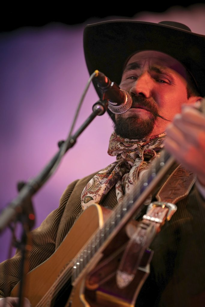 A man in a cowboy hat with goatee and handlebar moustache performs with a guitar