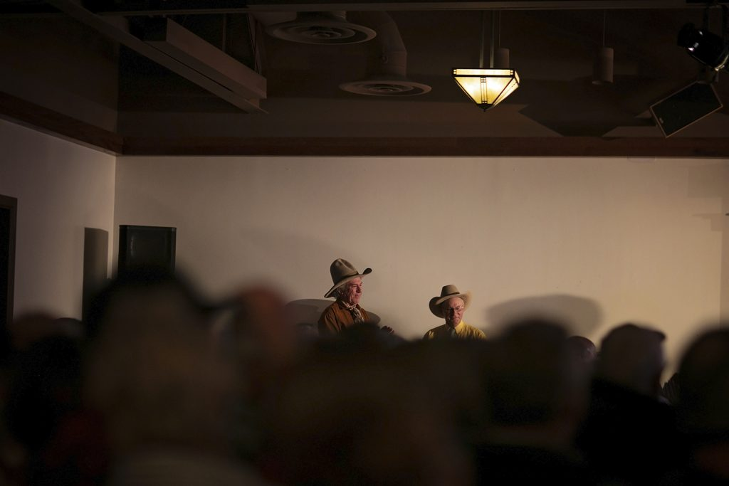Two elderly gentlemen in cowboy hats are visible behind the blurred heads of an attentive audience