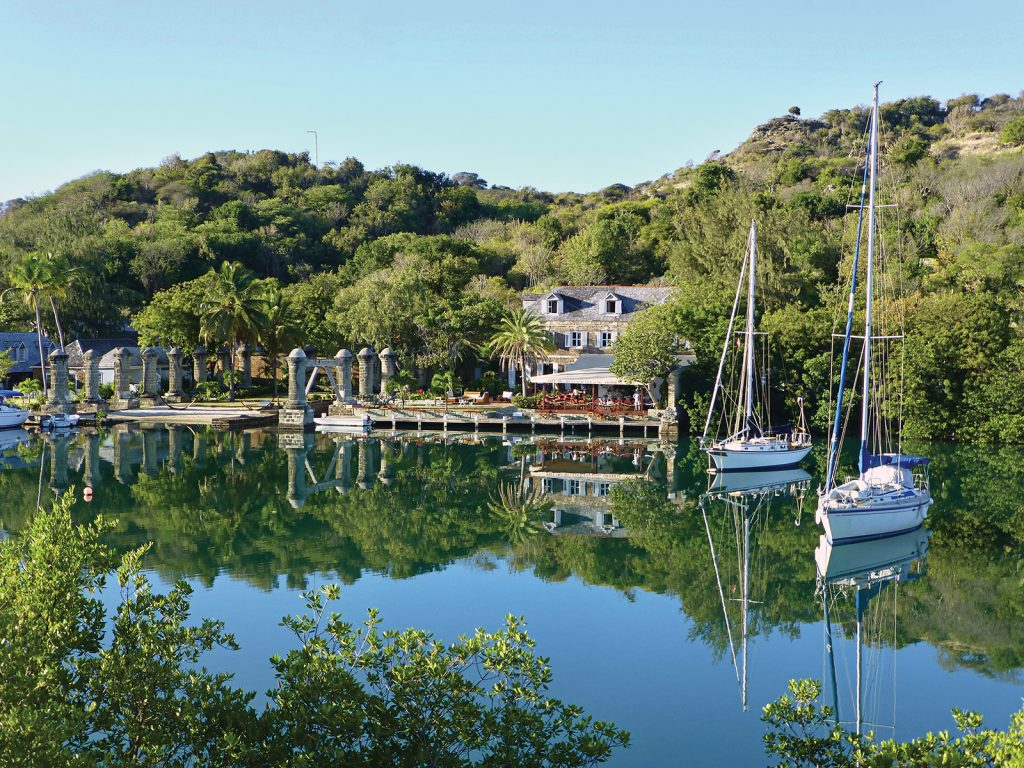 A peaceful tropical lagoon surrounded by lush trees, with sailboats at anchor