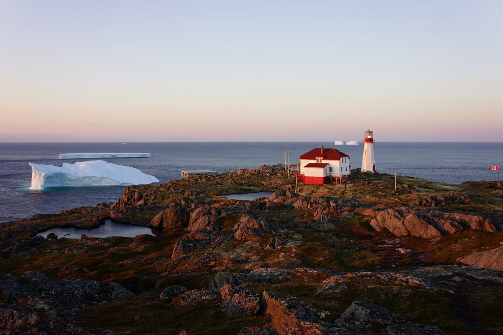 A large iceberg is seen off the rocky coast of an island with a lighthouse