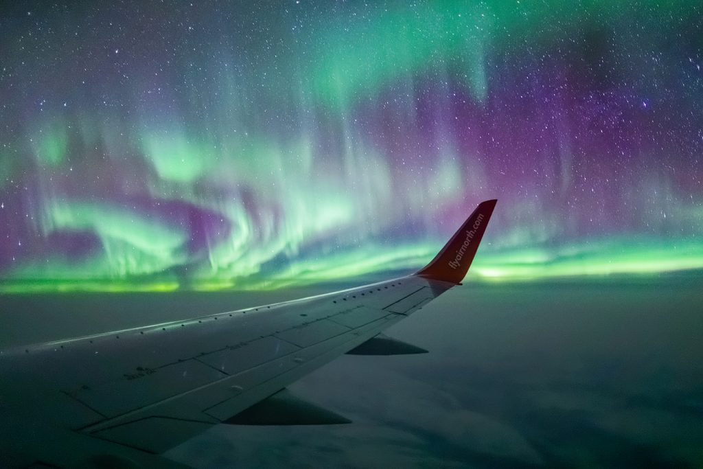 Airplane wingtip seen at night surrounded by green and purple aurora borealis