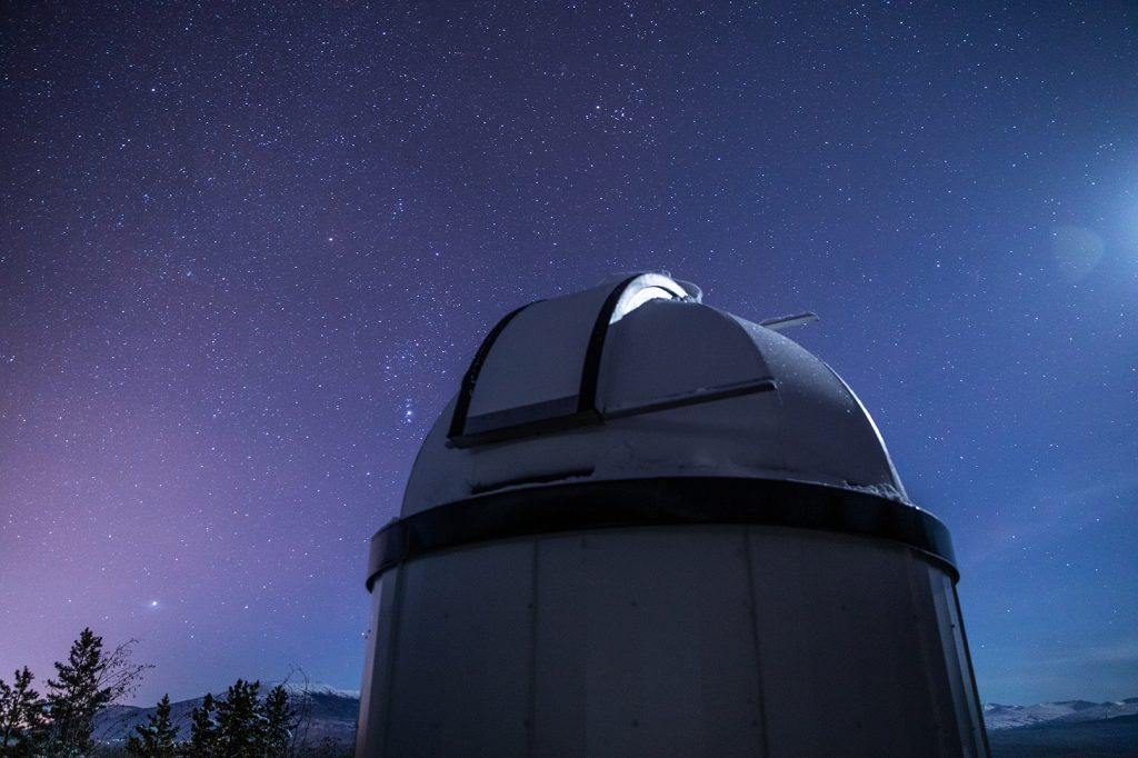 A telescope is silhouetted against a starry night sky