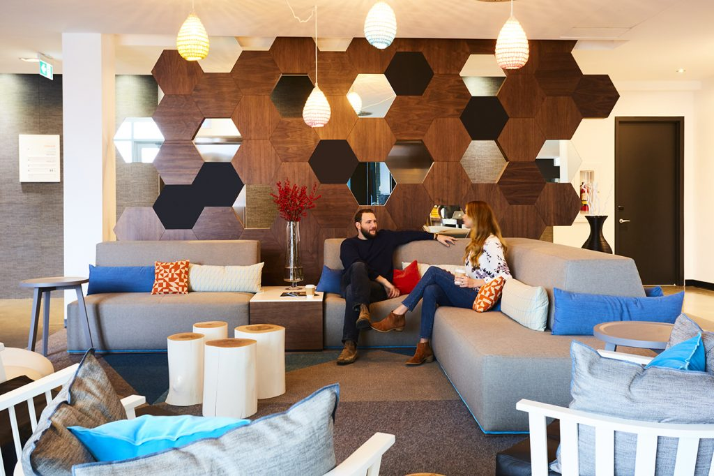 Cool hotel lobby with geometric panelling and sleek modern furniture