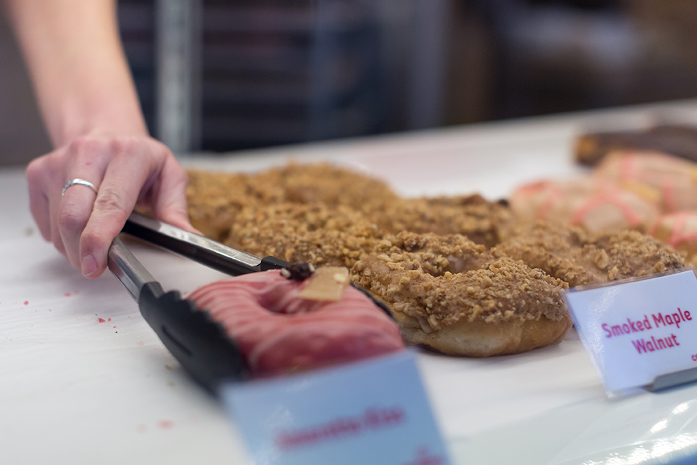 A person uses tongs to grab a donut from a display case