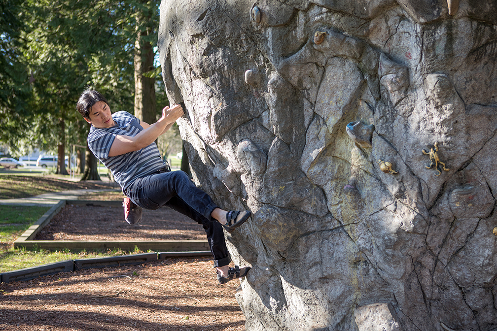 A man climbs a fake boulder in a park