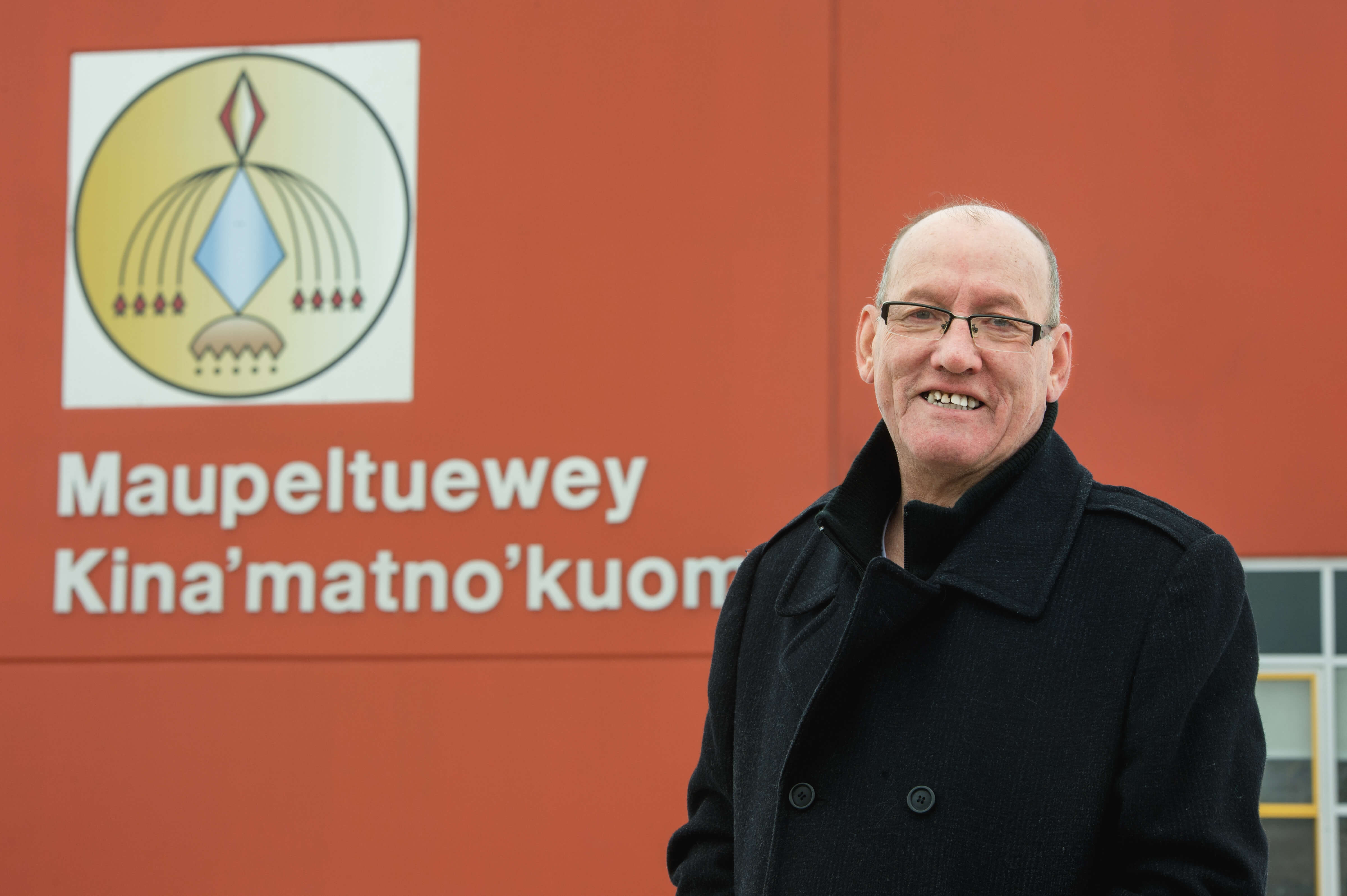 Man standing in front of a wall with a First Nation school name
