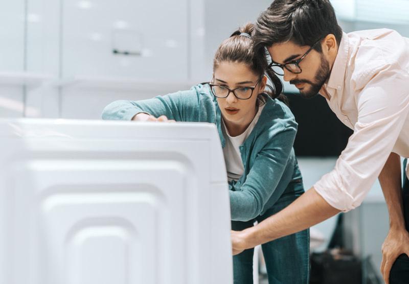 couple looking at washing machine