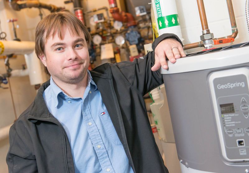 man posing by a water heater