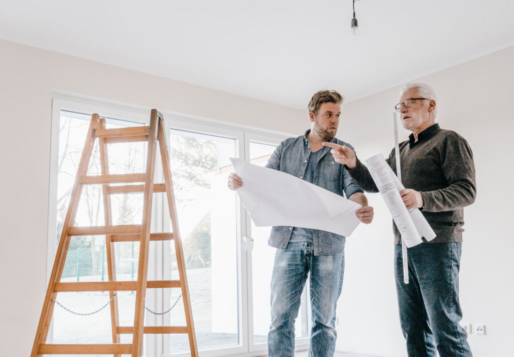 men with blueprints in home