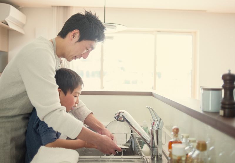 father and son washing dishes